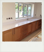 Oak kitchen doors with white granite work top.